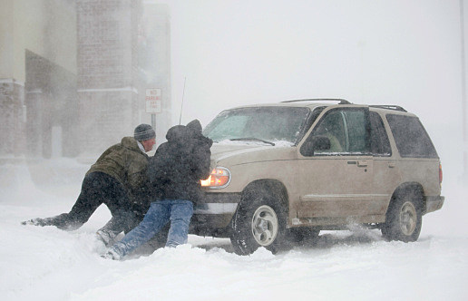 Two guys pushing out a car stuck in snow