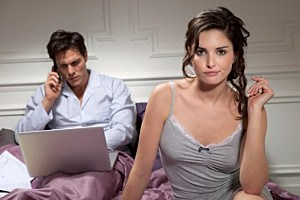 Man on a computer in bed, while his mate looks bored.