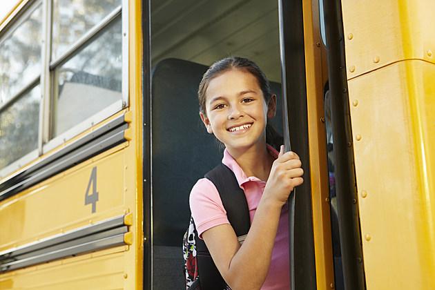 Pre teen girl getting on school bus