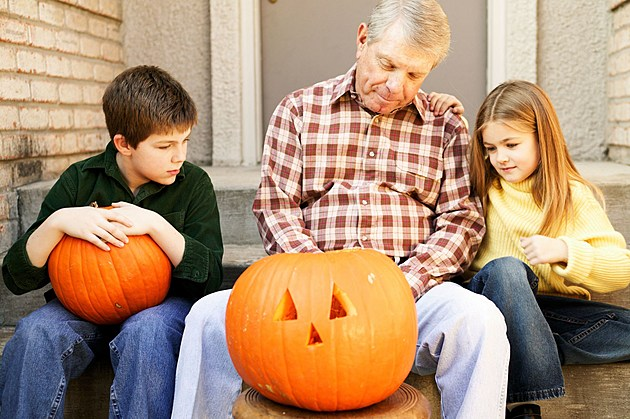 Grandfather carving pumpkin with grandkids